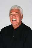 Attractive mature man laughing. Portrait of a handsome senior man royalty free stock photo