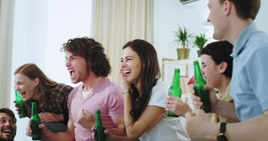 Attractive mature people closeup drinking beer cheers with bottles in front of the tv while watching a football match