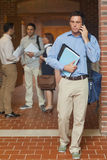 Attractive mature student phoning with his smartphone Royalty Free Stock Image