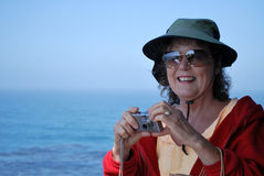 Traveling Woman. Attractive smiling tourist lady with big sunhat sunglasses red sweatshirt and a camera in hand with the open ocean in the background Stock Photo