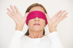 Attractive mature woman blindfolded Stock Images