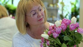 Attractive mature woman with bouquet of roses and tulips. Mature woman wearing eyeglasses hold beautiful bouquet of roses and tulips. Portrait of attractive stock video