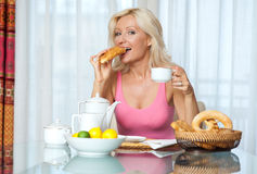 Attractive mature woman at breakfast Stock Photos