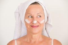 Attractive Mature Woman face creme Stock Photos