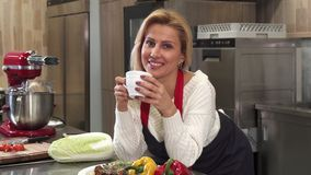 Attractive mature woman having coffee at the kitchen at home. Happy gorgeous mature housewife smiling joyfully to the camera enjoying drinking coffee at home stock image