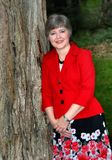 Business Suit on Woman. Attractive mature woman leans against a tree. She is dressed in a red dress jacket and patterned skirt. She has short hair royalty free stock photography