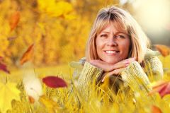 Mature woman in grass with aumn leaves Stock Photos