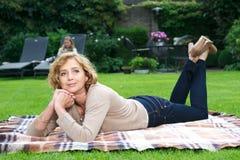 Attractive mature woman relaxing in garden Stock Image
