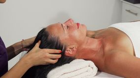 Attractive mature woman relaxing while receiving head massage. Cropped shot of a beautiful mature women receiving relaxing therapeutic head massage at spa center royalty free stock photo