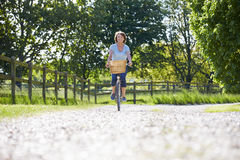 Attractive Mature Woman Riding Bike Along Country Lane Royalty Free Stock Photos