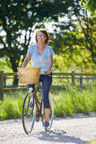 Attractive Mature Woman Riding Bike Along Country Lane Stock Photo