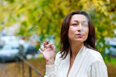 Attractive mature woman smoking outside Stock Images