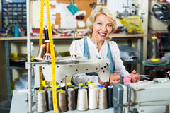 Attractive mature woman tailor using sewing machine Stock Photography