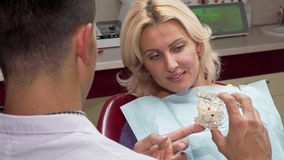 Attractive mature woman talking to the dentist at his office. Attractive mature women talking to the dentist at his office. Rear view shot of a professional stock images