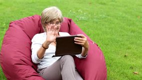 Attractive mature woman using digital tablet in a park stock footage