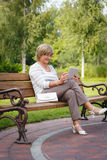 Attractive mature woman using digital tablet in a park Stock Image