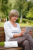 Attractive mature woman using digital tablet in a park Royalty Free Stock Photo