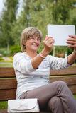 Attractive mature woman using digital tablet in a park Royalty Free Stock Image