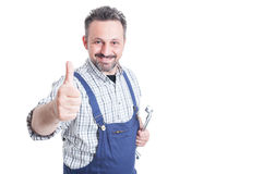 Attractive mechanic holding wrench and showing thumb up Royalty Free Stock Photo