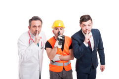 Attractive medic, engineer and businessman. Doing quiet gesture on white studio background Royalty Free Stock Images