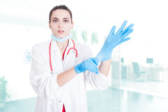 Attractive medic putting gloves on Stock Images