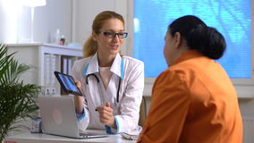 Attractive medical doctor is showing to female patient a X-ray picture on tablet stock footage
