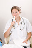 Attractive medical student. Young and attractive medical student in the practitioner's office Stock Image