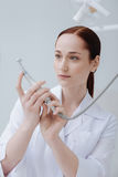 Attractive medical worker examining new instrument. Special tool. Very attentive dentist wearing white smock keeping arms bent in elbows while looking forward royalty free stock photography