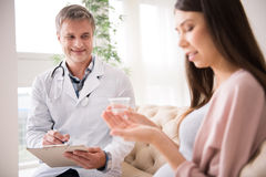 Attractive medical worker making notes. Just do it. Positive men keeping smile on his face and sitting near his patient while making prescription stock images