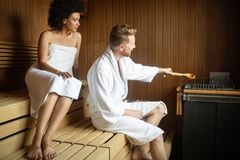 Attractive man and beautiful woman relaxing together in sauna. Attractive men and beautiful women relaxing together in sauna in hotel stock photo