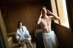 Attractive man and beautiful woman relaxing together in sauna. Attractive men and beautiful women relaxing together in sauna in hotel stock photos