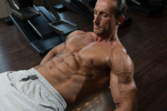 Attractive Men Doing Sit-Ups With Exercise Ball. Muscular Mature Man Exercising Abdominals On Exercise Ball In Modern Fitness Center Stock Photos