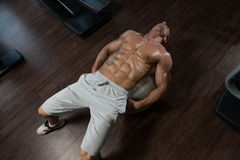 Attractive Men Doing Sit-Ups With Exercise Ball. Muscular Mature Man Exercising Abdominals On Exercise Ball In Modern Fitness Center Stock Image