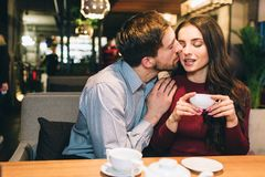 Attractive man is sitting with his girlfrien at the table and kissing her. She is holding a cup of tea and receiving a royalty free stock images