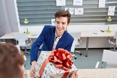 Portrait of joyful colleagues giving xmas presents to each other. Holiday concept. Attractive men smiling and giving xmas presents to colleaguaes. Smilling Stock Image