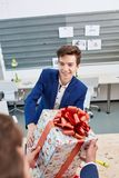 Portrait of joyful colleagues giving xmas presents to each other. Holiday concept. Attractive men smiling and giving xmas presents to colleaguaes. Smilling Stock Photo