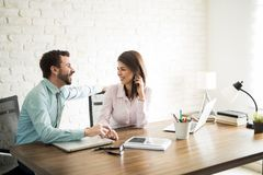 Man flirting with his coworker. Attractive men touching his female coworker`s hand and having a romantic office fling Royalty Free Stock Photo