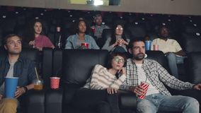 Attractive men and women watching film sitting in cinema with snacks and drinks. Attractive men and women millennials are watching film sitting in cinema with stock footage