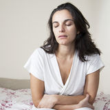 Attractive mid adult woman with stomach problems on bed Stock Photo