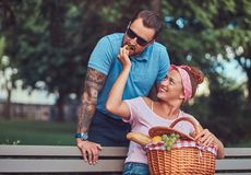 Attractive middle age couple during dating, enjoying a picnic on a bench in the city park. Attractive middle age couple during dating, enjoying a picnic on a Royalty Free Stock Image