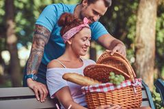 Attractive middle age couple during dating, enjoying a picnic on a bench in the city park. Attractive middle age couple during dating, enjoying a picnic on a Stock Image