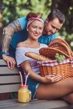 Attractive middle age couple during dating, enjoying a picnic on a bench in the city park. Attractive middle age couple during dating, enjoying a picnic on a Stock Photography
