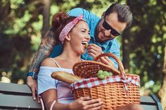 Attractive middle age couple during dating, enjoying a picnic on a bench in the city park. Attractive middle age couple during dating, enjoying a picnic on a Royalty Free Stock Photography