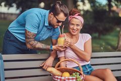 Attractive middle age couple during dating, enjoying a picnic on a bench in the city park. Attractive middle age couple during dating, enjoying a picnic on a Stock Photo