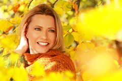 Attractive middle age woman in front of autumn leaves. Enjoys the last sun beams royalty free stock photography
