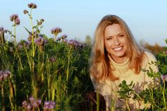 Attractive middle age woman sitting in a lilac flower field. In the evening sun royalty free stock images