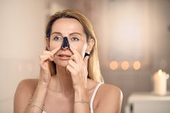 Attractive middle-aged blond woman applying an anti-aging face mask. To her nose in a bathroom with burning candles in a concept of beauty, skincare and the stock photos