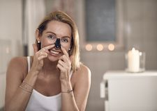 Attractive middle-aged blond woman applying an anti-aging face mask. To her nose in a bathroom with burning candles in a concept of beauty, skincare and the stock photo