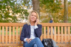 Attractive middle aged blond woman on a bench stock photo