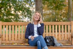 Attractive middle aged blond woman on a bench stock photos